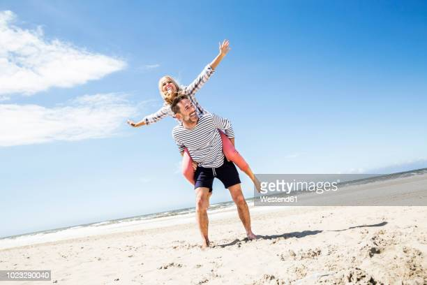 happy playful couple on the beach - arms outstretched stock pictures, royalty-free photos & images