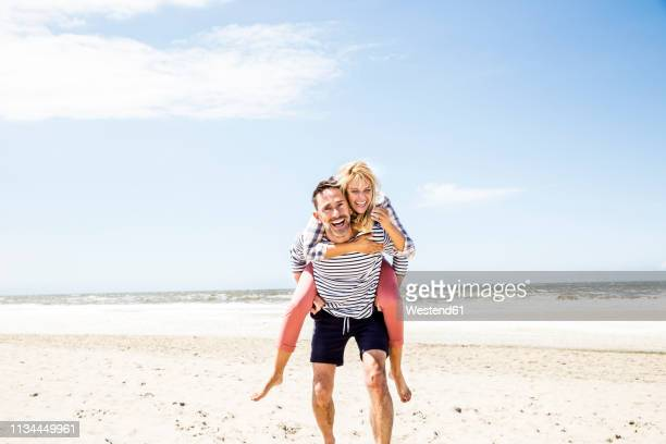 happy playful couple on the beach - heteroseksueel koppel stockfoto's en -beelden