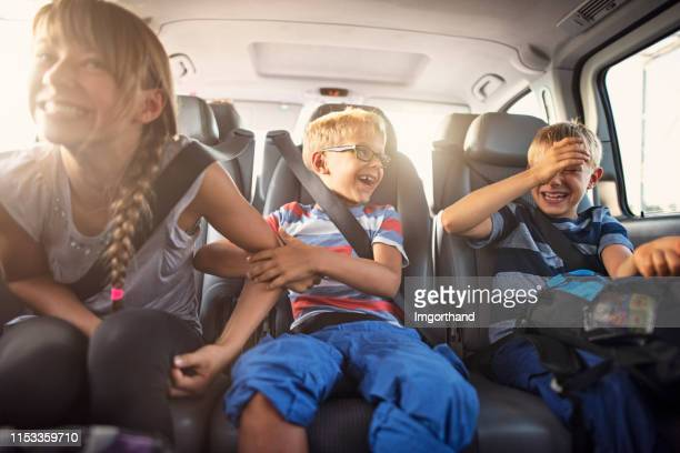 happy playful kids travelling by car - car stock pictures, royalty-free photos & images
