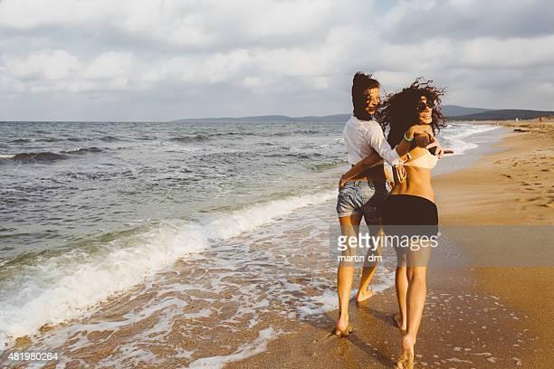 Happy playmates walking at the beach