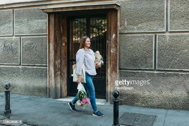 happy plus size woman walking on the street carrying a bag full of groceries and a flower bouquet - carrying stock pictures, royalty-free photos & images