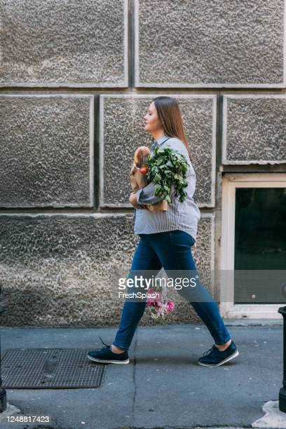 happy plus size woman walking on the street carrying flowers and groceries - side view stock pictures, royalty-free photos & images