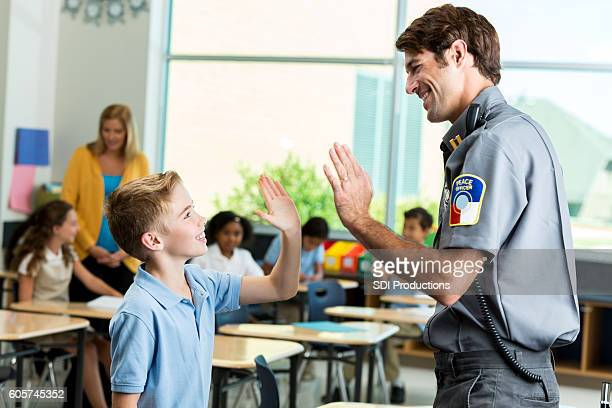 Happy police officer gives high five to student