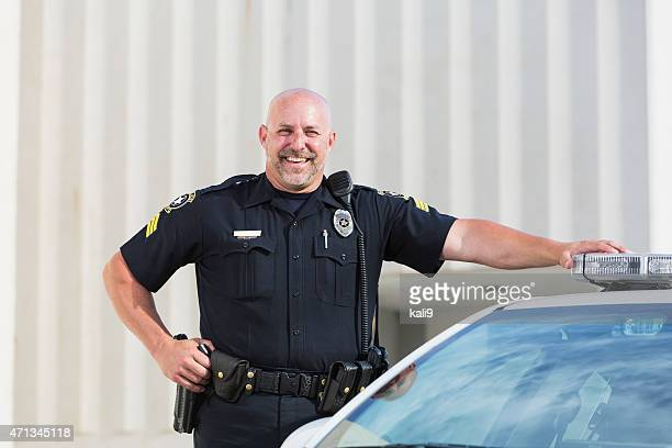 Happy police officer standing next to cruiser