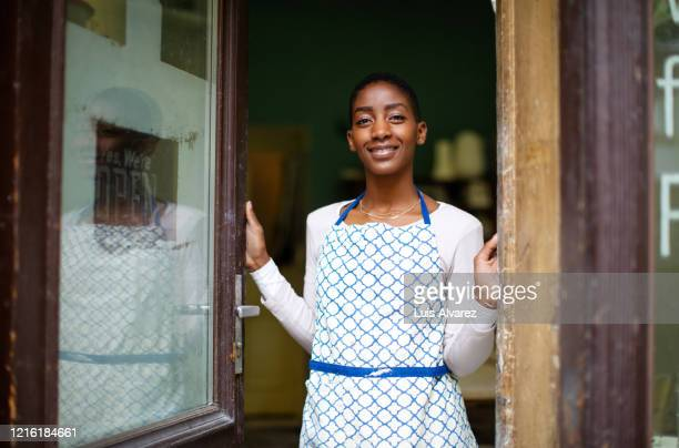 happy pottery studio owner at the entrance door - artist stock pictures, royalty-free photos & images
