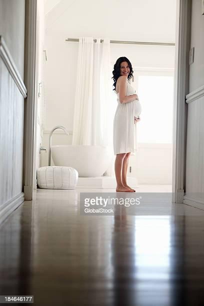 Happy pregnant woman in bathroom