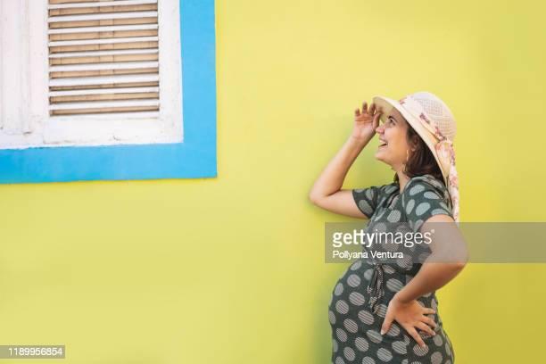 femme enceinte heureuse devant la fenêtre à la maison - grossesse humour photos et images de collection
