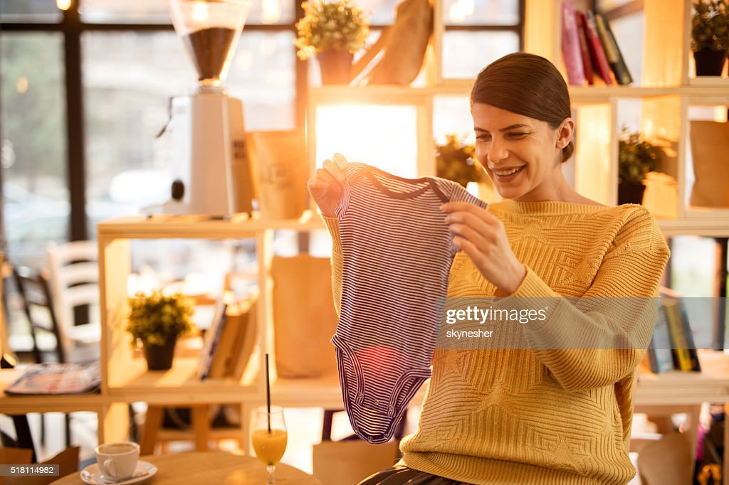 Happy pregnant woman looking at baby clothes in a cafe. : Stock Photo