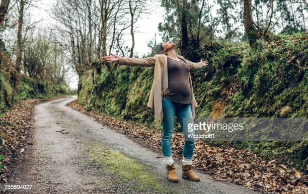 Happy pregnant woman raising her arms in forest in autumn