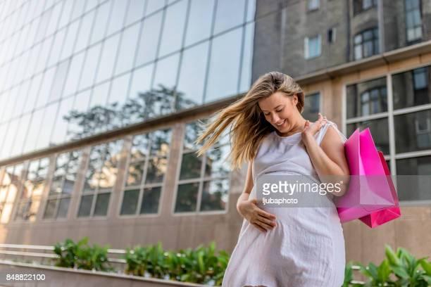幸せな妊娠中の女性のショッピング - マタニティウェア ストックフォトと画像