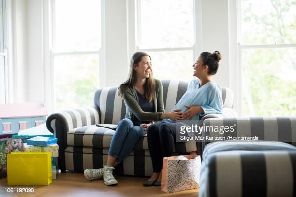 gelukkig zwangere vrouw zitten met vriend op bank - handen op de buik stockfoto's en -beelden