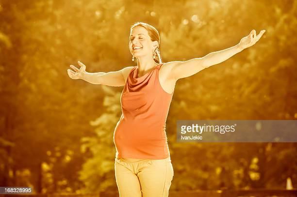 Glückliche schwangere Frau Ihre Arme Verbreitung