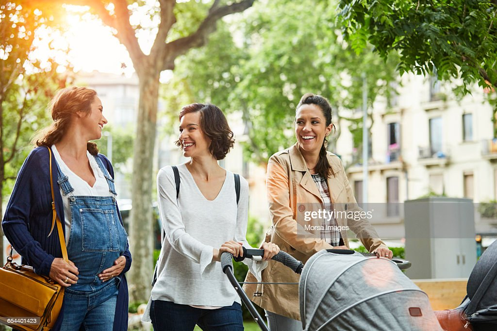 Happy pregnant woman with friends in park : Photo