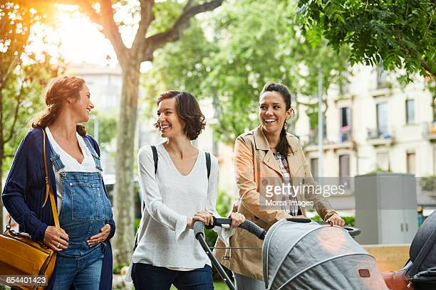 happy pregnant woman with friends in park - 30 39 years stock pictures, royalty-free photos & images