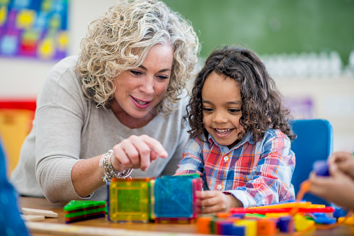 Happy preschool boy learns from his teacher 954812598