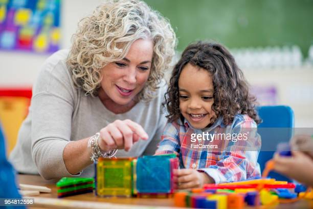 happy preschool boy learns from his teacher - child care stock pictures, royalty-free photos & images