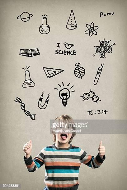 Preescolar niño feliz, con la ciencia y garabatos