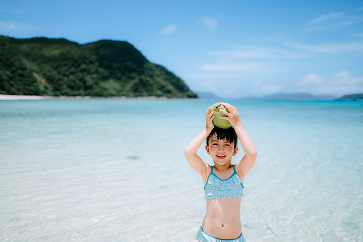 Happy preschool girl with coconut on tropical beach, Okinawa, Japan - gettyimageskorea