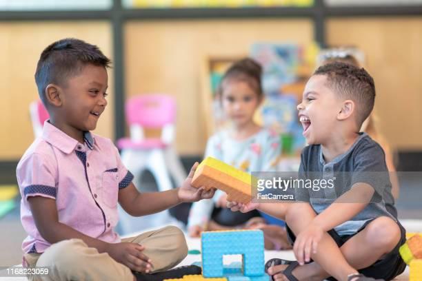 estudiantes de preescolar felices jugando juntos en el aula - compartir fotografías e imágenes de stock