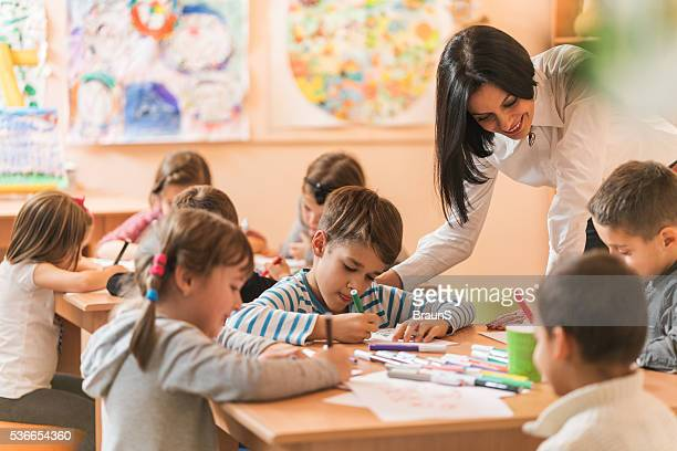Happy preschool teacher assisting children with their drawings.