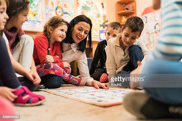 happy preschool teacher educating large group of children in kindergarten. - preschool building stock pictures, royalty-free photos & images