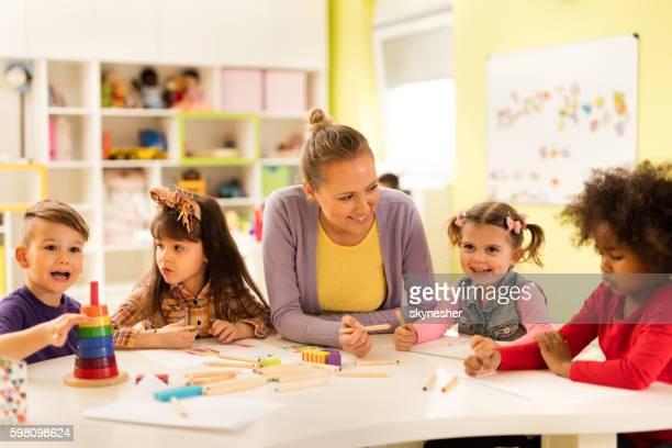 Happy preschool teacher having fun with kids during arts class.