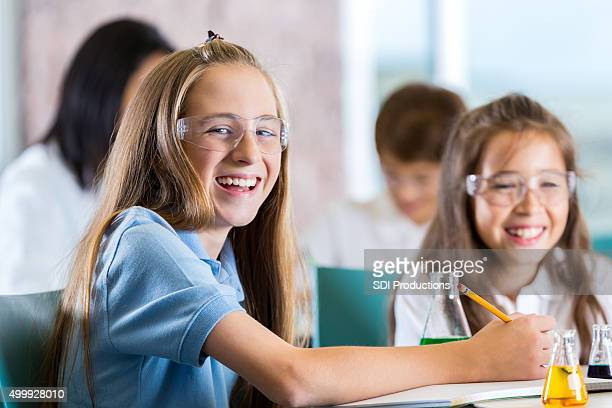 Happy preteen student taking notes in science class