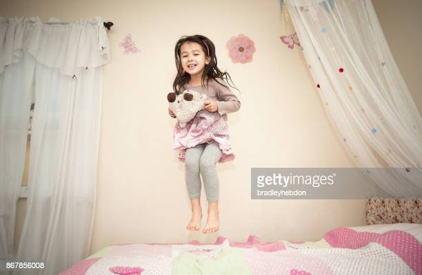 Happy pretty little girl jumping on her bed