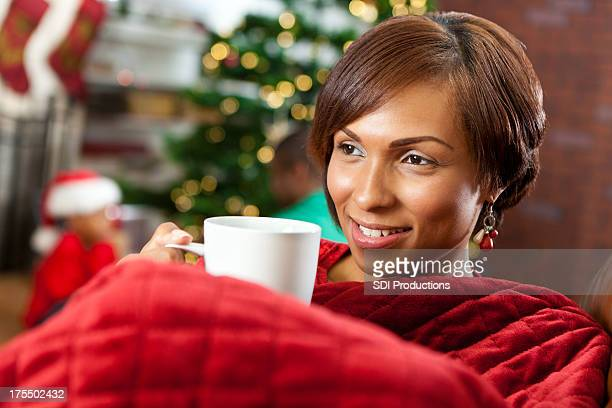 Happy pretty mother having coffee on Christmas morning with family