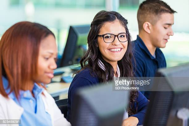 Happy private high school student using computer in modern classroom