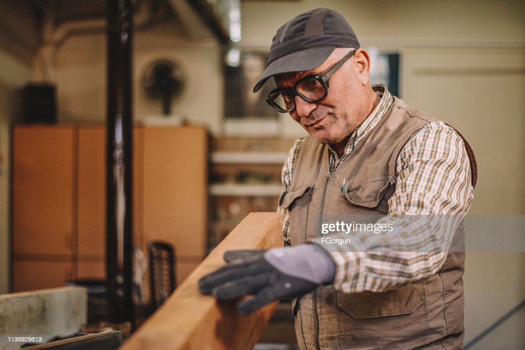 Happy professional craftsman in workshop with tools : Stock Photo