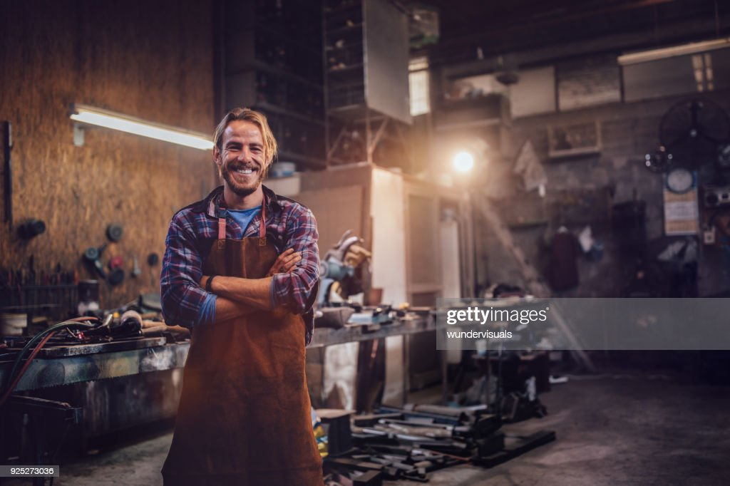 Happy professional craftsman standing in workshop with tools : Stock Photo