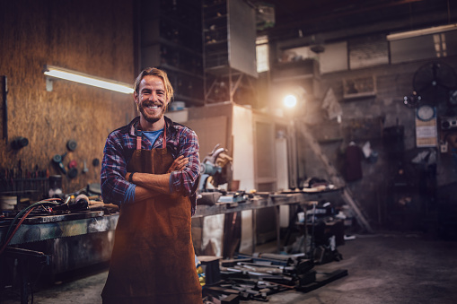 Happy professional craftsman standing in workshop with tools 925273036