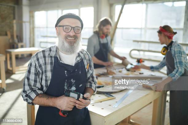 happy professional elderly carpenter in beanie hat and eyeglasses standing in factory shop and holding cordless screwdriver while looking at camera - satisfaction stock pictures, royalty-free photos & images