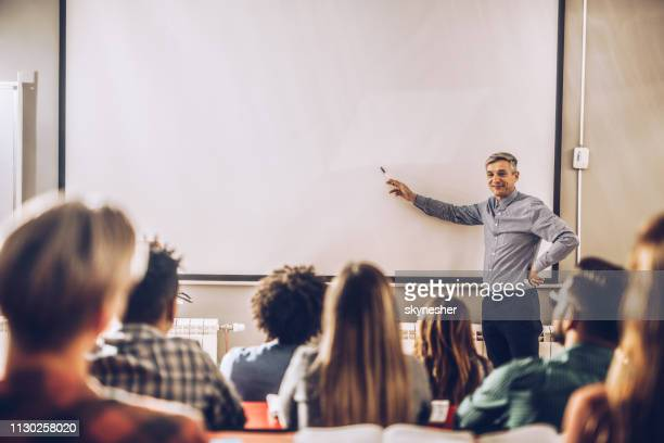 happy professor teaching a lecture on visual screen in the classroom. - projection equipment stock pictures, royalty-free photos & images