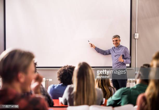 happy professor teaching a lecture on visual screen in the classroom. - mid adult stock pictures, royalty-free photos & images