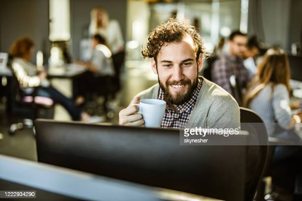 happy programmer drinking coffee while working on desktop pc in the office. - incidental people stock pictures, royalty-free photos & images