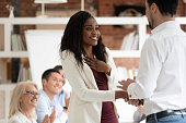Happy proud black female employee get rewarded handshake caucasian boss