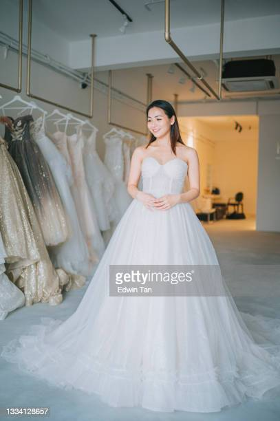 happy proud satisfied asian chinese bride portrait posing looking at camera smiling at bridal shop trying on wedding dress grown - wedding dress stock pictures, royalty-free photos & images