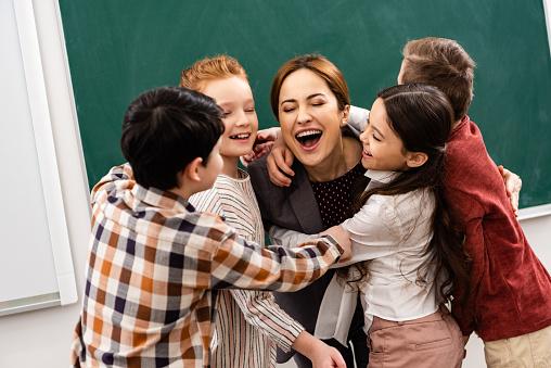 Happy pupils embracing teacher in front of blackboard in classroom 1149729035