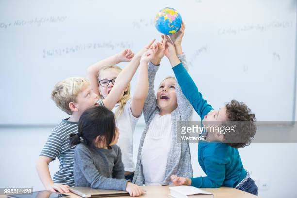 Happy pupils holding globe together in class