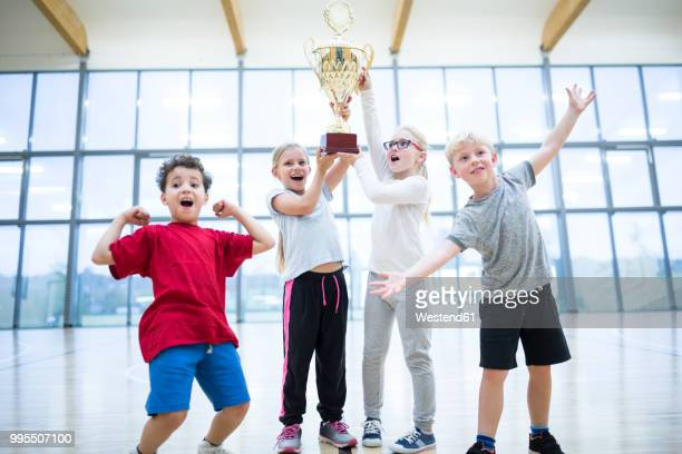 happy pupils holding trophy in gym - competition group photos et images de collection