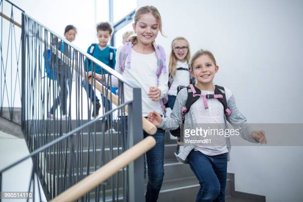 Happy pupils on staircase leaving school