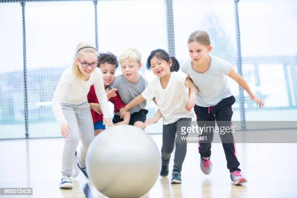 happy pupils playing with gym ball in gym class - physical education stock pictures, royalty-free photos & images