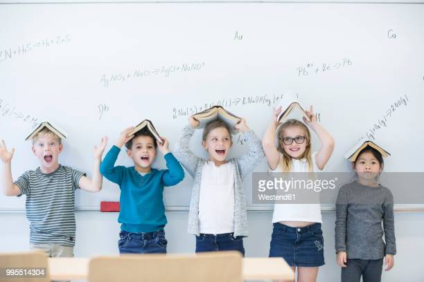 happy pupils with books above their heads standing at whiteboard with formulas in class - schulgebäude stock-fotos und bilder