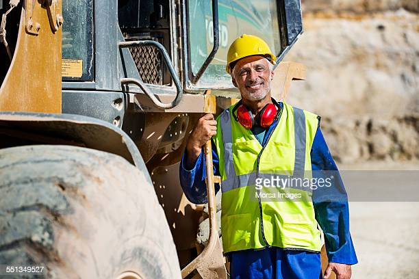 Happy quarry worker standing by bulldozer