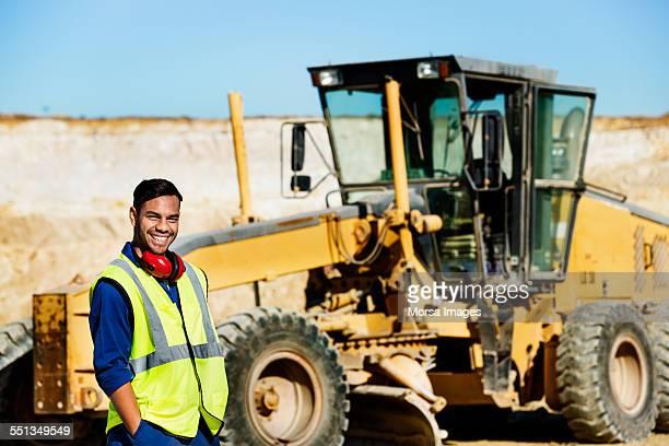 happy quarry worker standing by bulldozer - builder stock photos and pictures