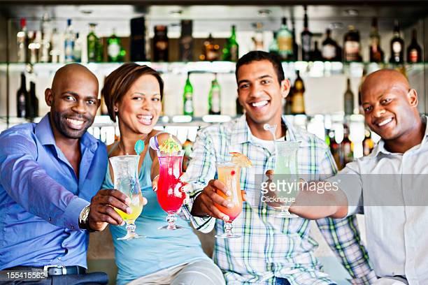 Happy quartet raise glasses in toast at bar