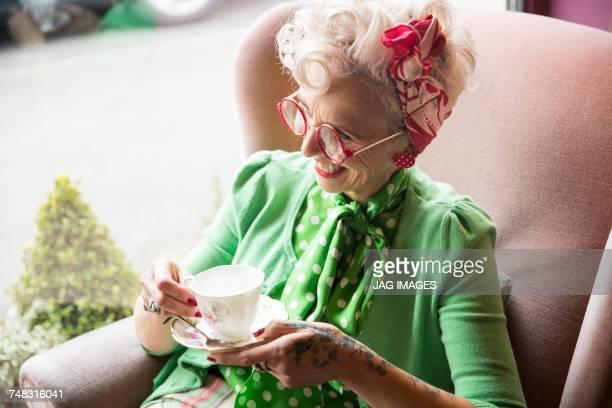 happy quirky vintage mature woman holding teacup and saucer in tea rooms - cultura británica fotografías e imágenes de stock