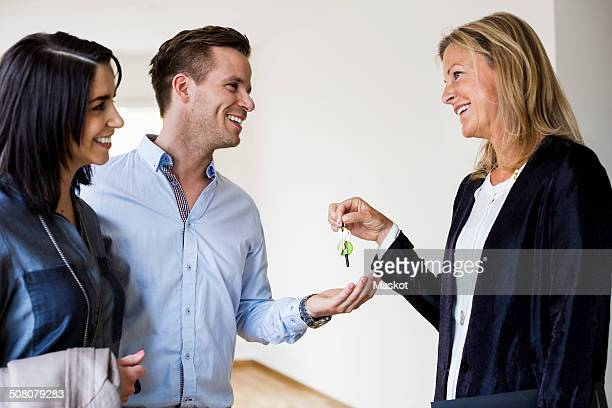 Happy real estate agent giving keys to couple in new house